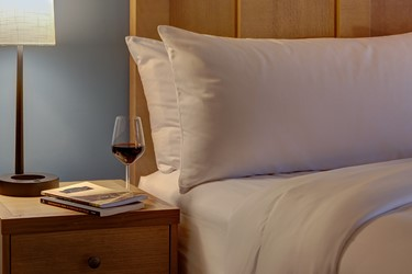 Wine and Book on Night Stand by Bed